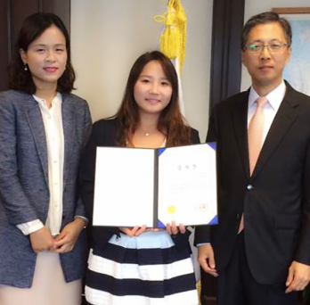 Hanae Kim holds her award while surrounded by representatives of the Ministry of Education