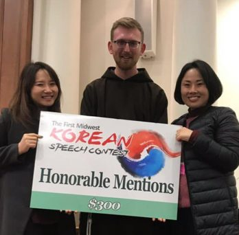 Joseph Babcock holds a sign declaring his award while flanked by UIC Korean instructors